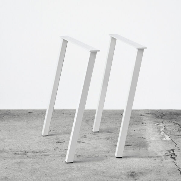 Hvide concav bordben i metal. Står frit på beton gulv foran en hvid væg