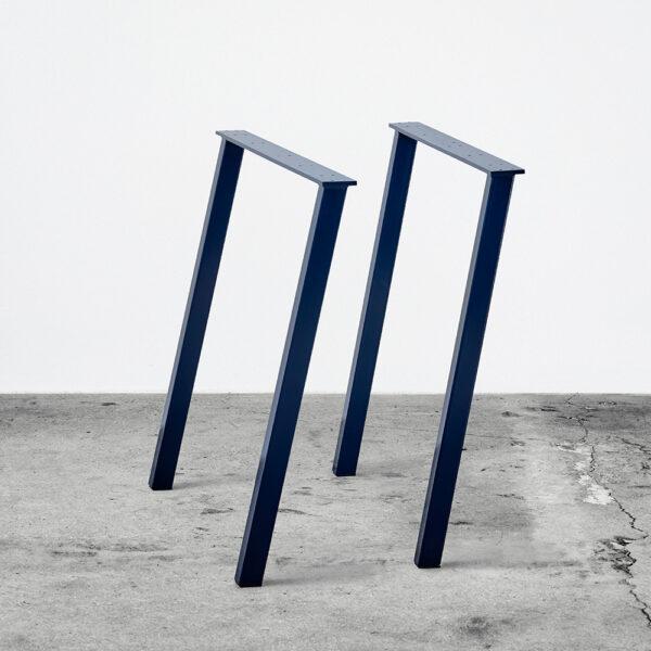 Midnightblue/blå concav bordben i metal. Står frit på beton gulv foran en hvid væg