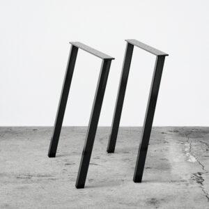 Sorte concav bordben i metal. Står frit på beton gulv foran en hvid væg