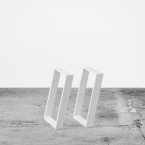 Hvide u-shaped concav bordben i metal til sofaborde og bænke . Står frit på beton gulv foran en hvid væg