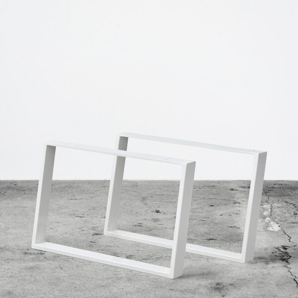Hvide u-shaped concav bordben i metal til sofaborde. Står frit på beton gulv foran en hvid væg