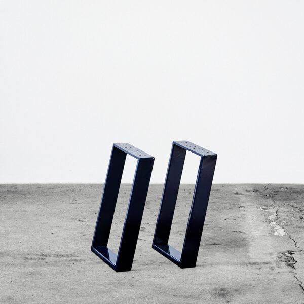 Midnightblue/blå u-shaped concav bordben i metal til bænke og sofaborde. Står frit på beton gulv foran en hvid væg