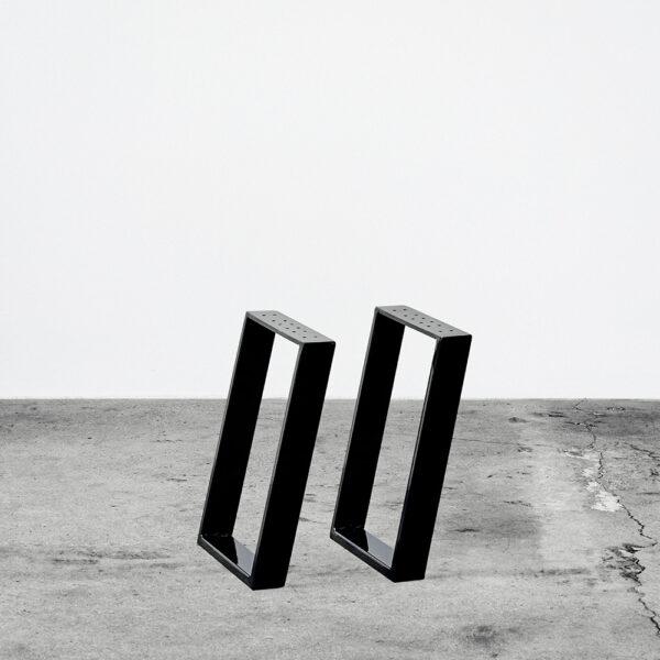 Sorte u-shaped concav bordben i metal til sofaborde og bænke. Står frit på beton gulv foran en hvid væg