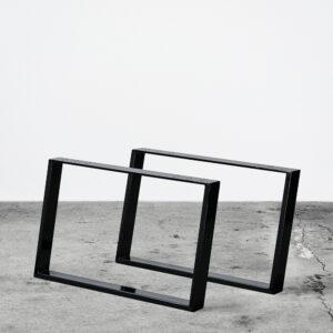 Sorte u-shaped concav bordben i metal til sofaborde. Står frit på beton gulv foran en hvid væg