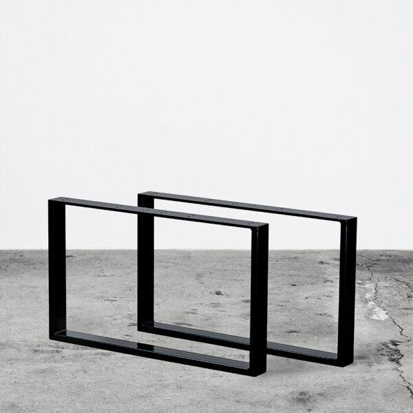 Sorte u-shaped bordben i metal til sofaborde. Står frit på beton gulv foran en hvid væg