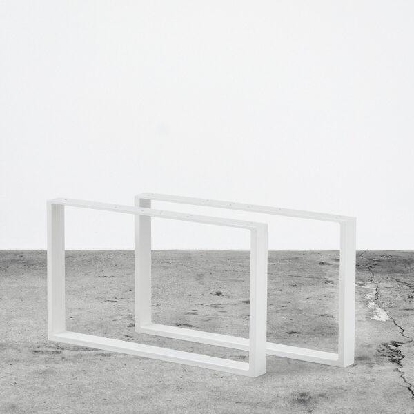 Hvide u-shaped bordben i metal til sofaborde. Står frit på beton gulv foran en hvid væg