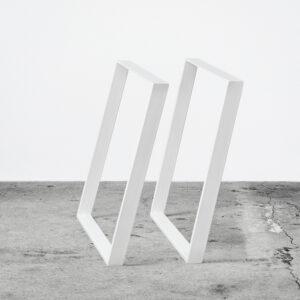 Hvide u-shaped concav bordben i metal. Står frit på beton gulv foran en hvid væg