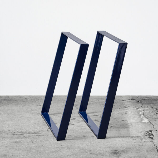 Midnightblue/blå u-shaped concav bordben i metal. Står frit på beton gulv foran en hvid væg