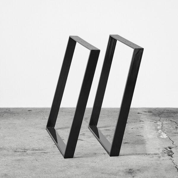 Sorte u-shaped concav bordben i metal. Står frit på beton gulv foran en hvid væg