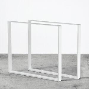 Hvide u-shaped bordben i metal. Står frit på beton gulv foran en hvid væg