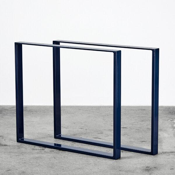 Midnightblue/blå u-shaped bordben i metal. Står frit på beton gulv foran en hvid væg