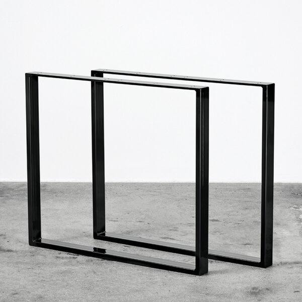 Sorte u-shaped bordben i metal. Står frit på beton gulv foran en hvid væg