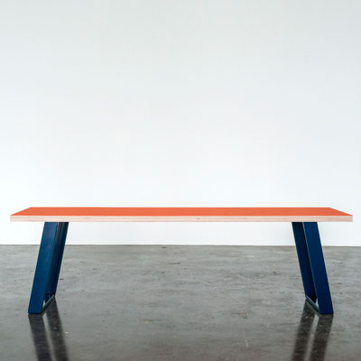 Bænk med Orange Blast farvet linoleum og Midnight Blue u-shaped concave bænkben der står på et beton gulv foran en hvid væg