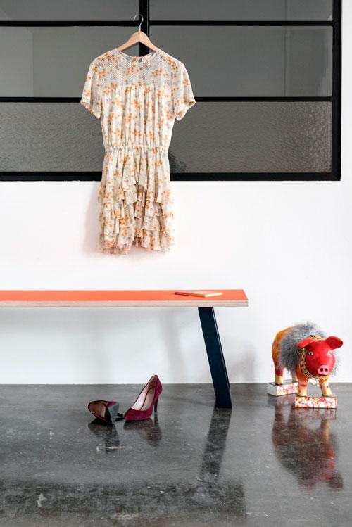 Bænk med Midnight Blue bordben, kjole, sko og kunst-gris foran en hvid væg med vinduer