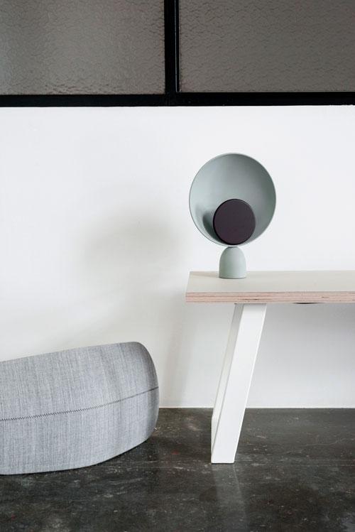 Hvide bordben med en lys linoleums plade foran en hvid væg med vinduer.