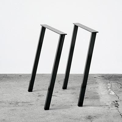 Sorte concave bordben i metal. Står frit på beton gulv foran en hvid væg