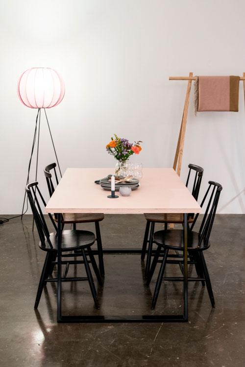 Linoleumsspisebord med sorte bordben, med bloster og lampe foran en hvid væg