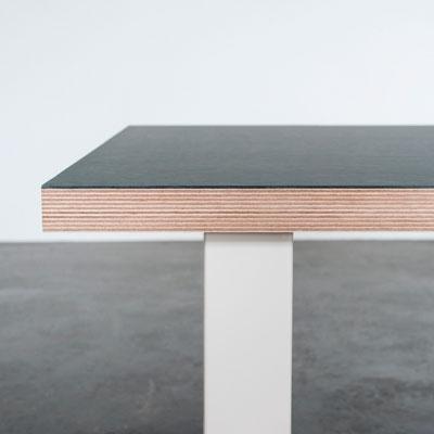 Bordplade med mørk linoleum og hvide bordben der står på et beton gulv foran en hvid væg