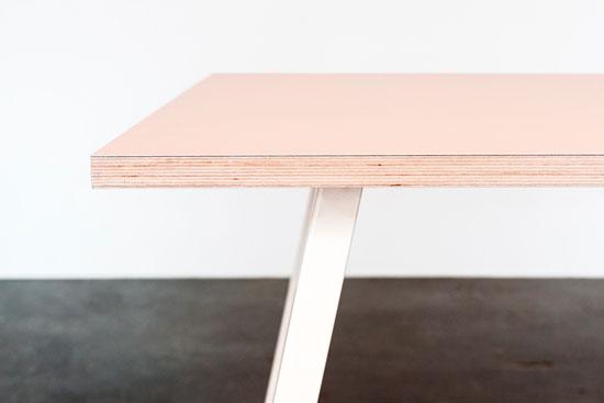 Hvide bordben med en Powderfarvet linoleums plade, står på et beton gulv foran en hvid væg