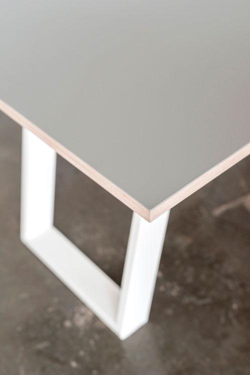 Lys linoleums plade på hvide bordben der står på et beton gulv