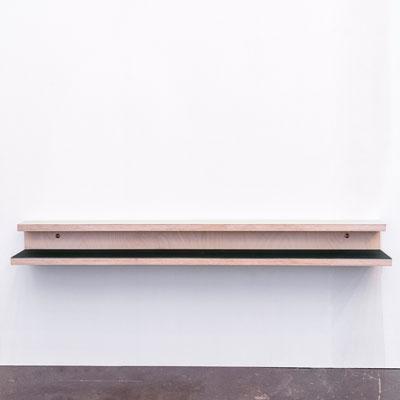 Skohylde med linoleum i forskellige farver, hænger på en hvid væg over et beton gulv