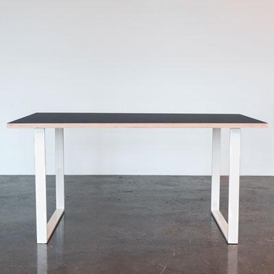 Skrivebord med mørk linoleum og hvide u-shaped bordben der står på et beton gulv foran en hvid væg