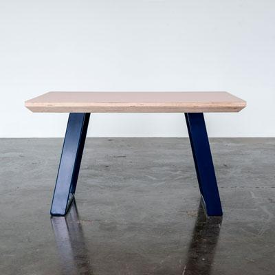 Sofabord med Powder farvet linoleum og Midnight Blue u-shaped concave sofabordben der står på et beton gulv foran en hvid væg