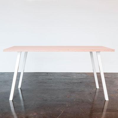 Spisebord med powder farvet linoleum og hvide concave bordben der står på et beton gulv foran en hvid væg