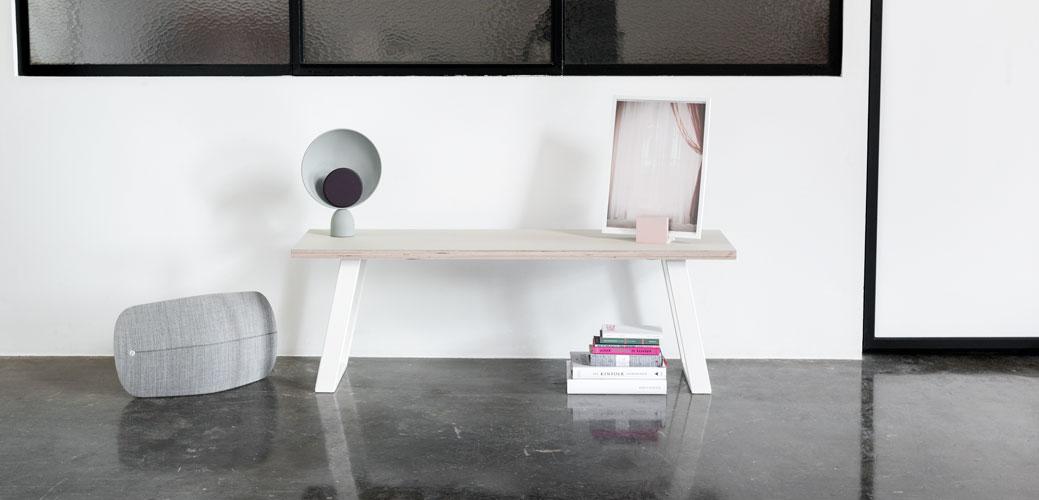 Bænk med hvide u-shaped concave bænkben på et betongulv med bøger og højtaler