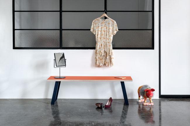 Bænk med blå u-shaped concave bænkben på et betongulv med sko og kjole