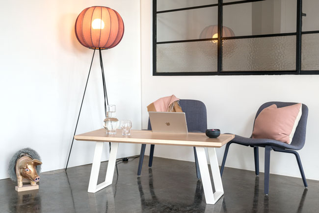 Hyggekrog med lamelbordplade og hvide u-shaped concave bordben med to lænestole og en designer lampe