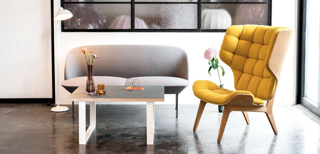 Hyggekrog med sofabord, gul stol og grå sofa.
