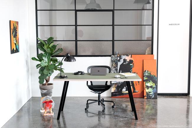Kontor indretning med skrivebord med sort concave bordben og linoleums bordoplade der står på et beton gulv foran en hvid væg med vinduer