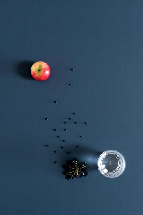 Linoleums bordplade med æble, bær og vandglas