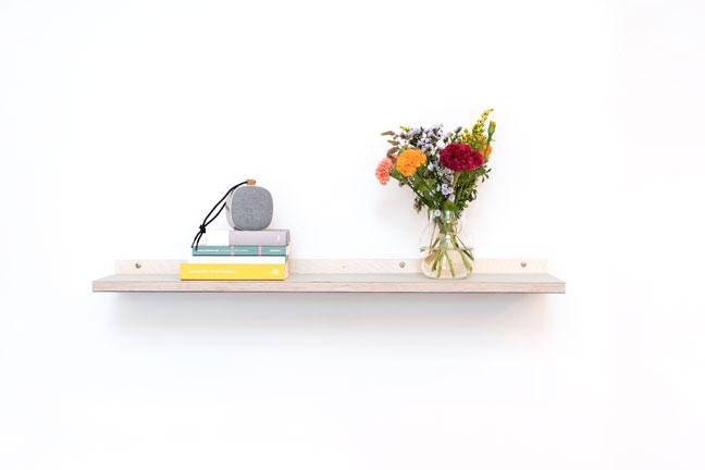 Enkelt linoleums hylde med blomster, bøger og højtaler. Hænger på en hvid væg