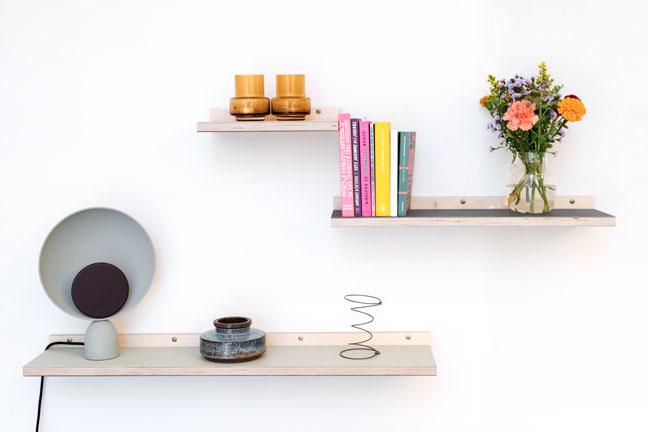 Linoleums hylder med bøger, nips, blomster og lampe. Hænger på en hvid væg