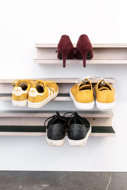 Skohylder på en hvid væg med forskellige farver linoleum og 4 par sko