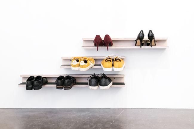 Skohylde med flere farver linoleum ophængt på en hvid væg