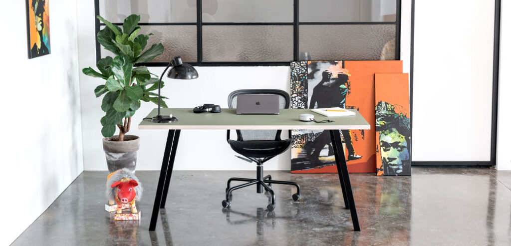 Skrivebord med sort concave bordben og linoleums bordoplade der står på et beton gulv foran en hvid væg med vinduer