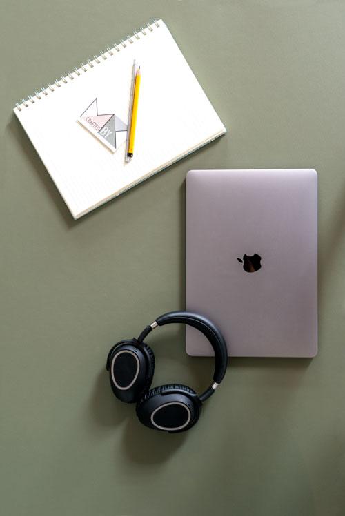 Skrivebord med linoleums bordplade hvor der ligger en blok, computer og hovedtelefoner