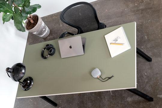 Linoleums skrivebord med sorte concave bordben hvor der ligger højtaler, blok, computer og hovedtelefoner