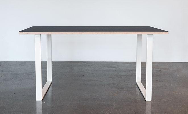 Spisebord med linoleums bordplade og hvide u-shaped bordben der står på et beton gulv foran en hvid væg