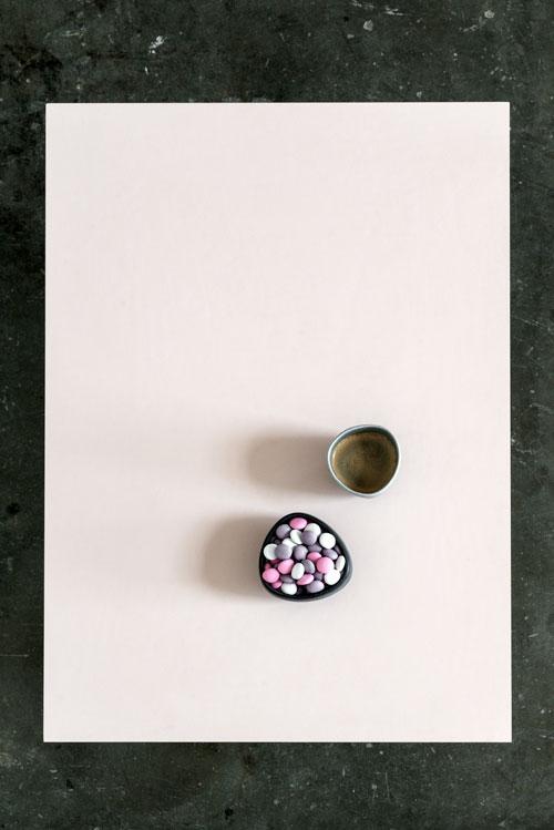 Spisebord med powder farver linoleums bordplade hvor der står en kop kaffe og en skål slik