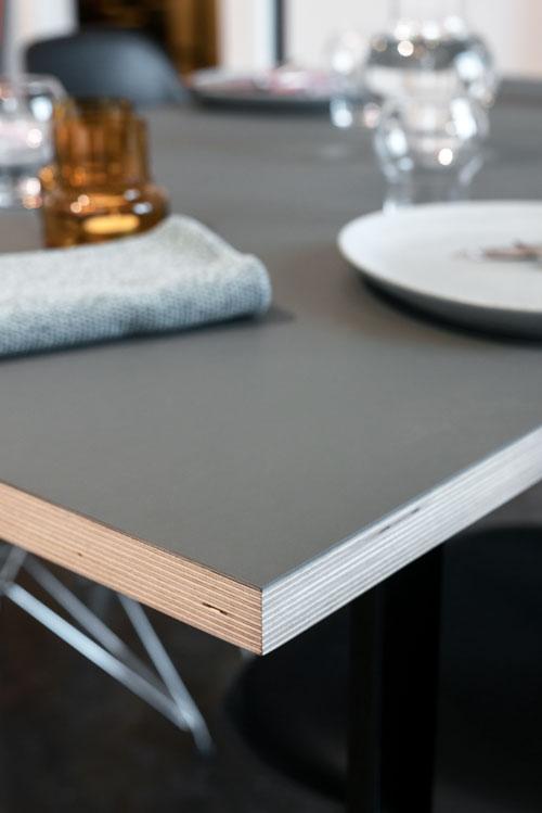 Spisebord set fra hjørnet med grå linoleum og dækket med tallerken, glas og serviet