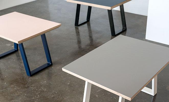 Tre linoleums sofaborde på et beton gulv foran en hvid væg. Alle sofaborde er med forskellig farve linoleum og borden.