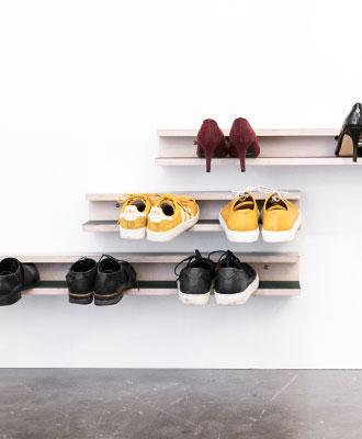 Tre skohylder på en hvid væg med forskellige farver linoleum og sko