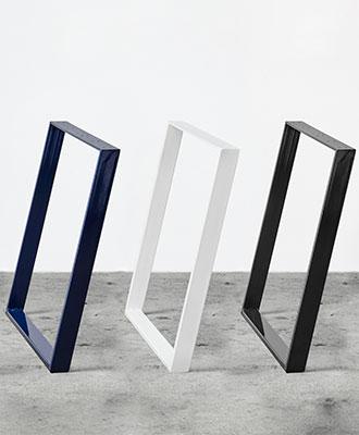 Tre bordben i hver deres farve, sort, hvid og midnight blue, der alle står på et beton gulv foran en hvid væg