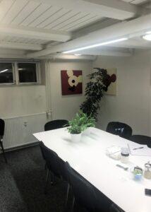 Før billede af mødelokale med hvidt bord og grå stole
