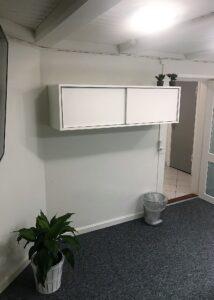 Før billede af mødelokale med opbevaringsskab på væggen