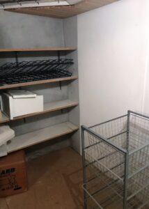 Før billede af reolvæg i opbevaringsrum i kælderen